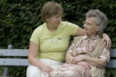 Mother &  daughter. Portrait of elderly woman with her daughter on the the park bench Royalty Free Stock Photo
