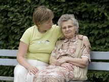Mother &  daughter. Portrait of elderly woman with her daughter on the the park bench Royalty Free Stock Image