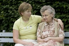Mother &  daughter. Portrait of elderly woman with her daughter on the the park bench Royalty Free Stock Images