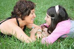 Mother and daughter. Lie on the grass and look at each other Royalty Free Stock Photo