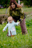 Mother with daughter. Mother helping to make first steps to her small child royalty free stock photos