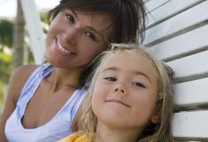 Mother and daughter. Portrait of mother and daughter sitting on the bench Stock Image