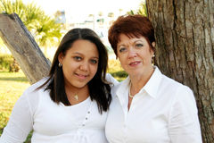 Mother and daughter. Caucasian middle aged mother with mixed race adopted daughter outside Royalty Free Stock Photos