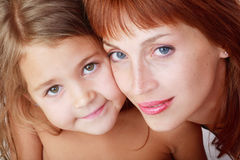 Mother and daughter. Close-up portrait of beautiful red-haired mother and cute daughter Royalty Free Stock Photos
