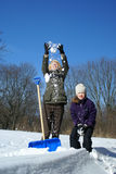 Mother and daughter. Shoveling and have fan outside Stock Images
