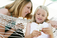 Mother and Daughter. A mother talking to her daughter sitting on a hammock holding a white flower Royalty Free Stock Image