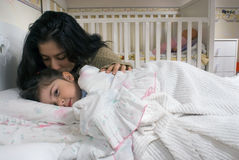 Mother and Daughter. Little girl pretending to be asleep but looking at the camera with a mischievous eye as her mother gives her a goodnight kiss Stock Images