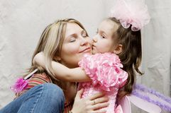 Mother And Daughter. Family portrait little daughter kissing her mother royalty free stock photos