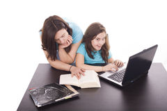 Mother and daughter. Mother reading a book and daughter working with a laptop Stock Image