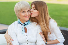 Mother and daughter. Adult mother and daughter in a cafe on the street. Daughter kissing smiling mother on the jowl Stock Photos