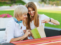 Mother and daughter. Adult mother and daughter are considering buying after shopping. They are sitting in a cafe outside Royalty Free Stock Photos