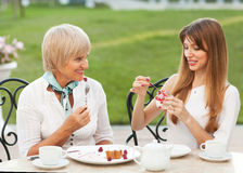 Mother and daughter. Adult mother and daughter drinking tea or coffee and talking outdoors Royalty Free Stock Photography