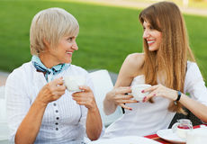 Mother and daughter. Adult mother and daughter drinking tea or coffee and talking outdoors Stock Image