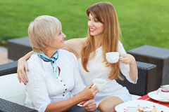Mother and daughter. Adult mother and daughter drinking tea or coffee and talking outdoors Royalty Free Stock Photo