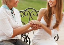 Mother and daughter. Adult mother and daughter holding hands, talking outdoors Royalty Free Stock Image