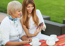 Mother and daughter. Adult mother and daughter. The daughter on the phone shows a photo of the fiance. They drink coffee and tea Stock Image