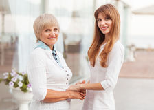 Mother and daughter. Adult mother and daughter standing at the large glass case holding hands. They are dressed in white dresses Stock Image