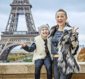 Mother and daughter against Eiffel tower showing victory Stock Photography