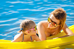 Mother and daughter on airbed. Mother and daughter in sunglasses floating on airbed together royalty free stock images