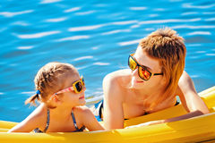 Mother and daughter on airbed. Mother and daughter in sunglasses floating on airbed together royalty free stock photos
