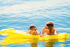 Mother and daughter on airbed. Mother and daughter in sunglasses floating on airbed together royalty free stock photography