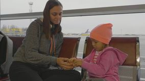 Mother and daughter at airport. Little girl cleans mandarin at waiting hall. Mother and daughter at airport. Little girl cleans mandarin at waiting hall, slow stock footage