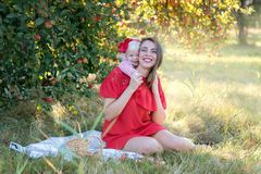 Mother with daughter in an apple orchard Stock Photo