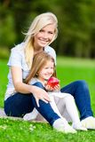 Mother and daughter with apple sitting on the green grass Stock Photography