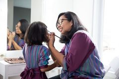 Mother and daughter applying make up together stock images