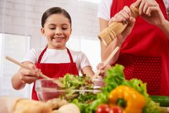 Mother and daughter in aprons mix salad royalty free stock photography