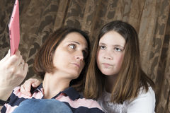 Mother and daughter arguing and holding tablet stock images