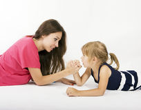 Mother and daughter arm wrestling (difficult parenting). Mother and child wrestling (difficult child Stock Image