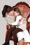 Mother and daughter in Armchair. A happy smiling daughter sitting on the lap of her mother in an pink Royalty Free Stock Photo