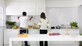 Mother and daughter arrange tools. Time lapse video, mother and daughter arrange tools in new modern white kitchen stock footage