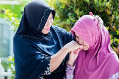 Mother and daughter from Asia forgive each other. During ied or Islamic celebration Stock Photos