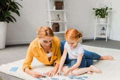 Mother and daughter assembling puzzle. On floor at home Stock Image