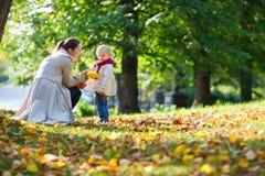 Mother and daughter at autumn park Stock Photos