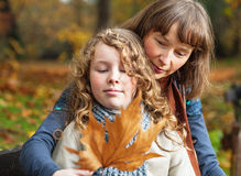 Mother and daughter in an autumn park. Mother and her teenager daughter sitting on a bench in an autumn park and looking at fallen leaf Stock Photo