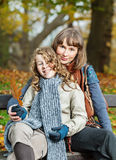 Mother and daughter in an autumn park. Smiling mother and her teenager daughter sitting on a bench in an autumn park Stock Image