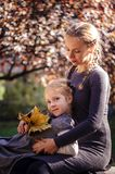 Mother with daughter in the autumn park. Mother with little daughter dressed in grey clothes walking in the autumn park Stock Photo