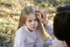 Mother and daughter in the autumn park. Mom gently stroking her daughter's head sitting in autumn park Stock Photography