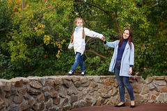 Mother and daughter in autumn park. Royalty Free Stock Image