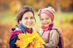 Mother and daughter in the autumn park. Smiling little girl and her mother enjoy walk in autumn park and play with bright autumn leaves Royalty Free Stock Images