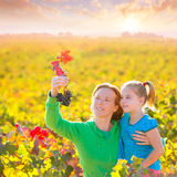 Mother and daughter on autumn vineyard smiling holding grape Stock Photo