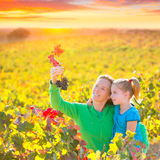 Mother and daughter on autumn vineyard smiling holding grape Royalty Free Stock Photo