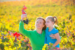 Mother and daughter on autumn vineyard smiling holding grape Stock Image