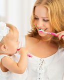 Mother and daughter baby girl brushing their teeth together Royalty Free Stock Photo