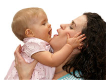 Mother daughter baby talk. Close-up of mother and baby daughter interacting with baby's hand on mother's face Stock Images