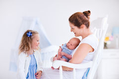 Mother with daughter and baby in a white nursery. Little sister hugging her newborn brother. Toddler kid meeting new sibling. Mother and new born baby boy relax Royalty Free Stock Photo