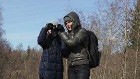 Mother and daughter with backpack and binoculars on forest road stock footage